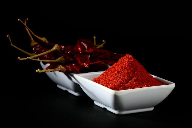 Холодный порошок с красным чили в белой тарелке, сушеный перец на черном фоне