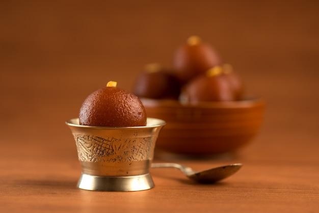 グラブジャムンボウルと銅のアンティークボウルにスプーン。インドのデザートまたは甘い料理。