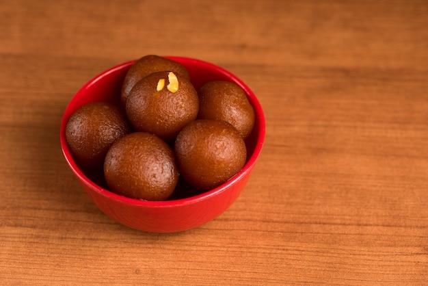 木製のテーブルの赤いボウルでガラブジャムン。インドのデザートまたは甘い料理。