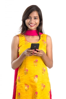 Молодая индийская девушка с помощью мобильного телефона или смартфона, изолированных на белом фоне