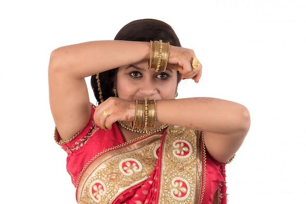 Красивая маленькая девочка представляя в индийском традиционном сари на белой предпосылке.