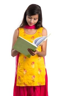 Хорошенькая молодая девушка держит книгу и позирует на белом фоне