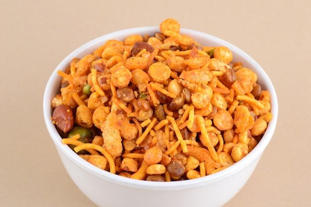 Индийские закуски: смесь (жареные орехи с солью, перцем масала, бобовые, зелёный горошек чанна масала дал) в синей миске в