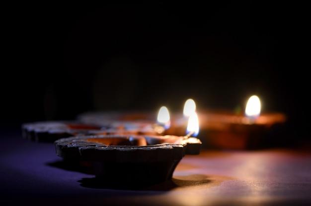 ディワリ祭のお祝い中にカラフルな粘土ディヤ(ランタン)ランプが点灯します。グリーティングカードデザインインドのヒンズー教の光の祭典と呼ばれるディワリ祭。