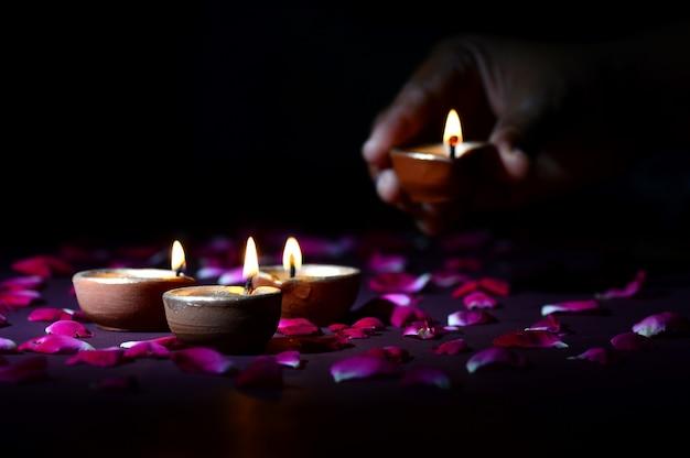 ライトのディワリ祭中にランタン(ディヤ)を保持し、配置する手