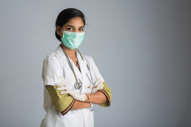 Портрет доктора женщины нося защитную маску и перчатки с стетоскопом. мировая эпидемия коронавирусной концепции.