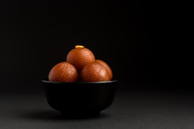 Гулаб джамун в миске. индийский десерт или сладкое блюдо.
