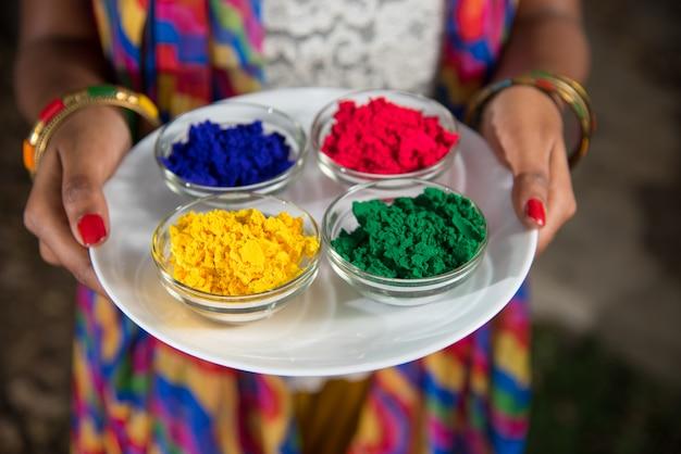 Молодая девушка держит порошковые краски в тарелке на фестивале цветов под названием холи, популярный индуистский фестиваль, который отмечается по всей индии