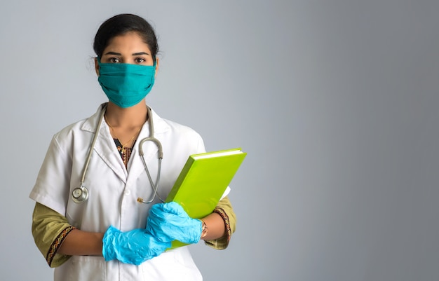 医療報告書または本でポーズと兆しを見せ美しい若い女性医師。