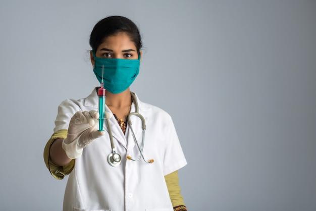 Женщина-врач со стетоскопом держит и показывает инъекцию или шприц.