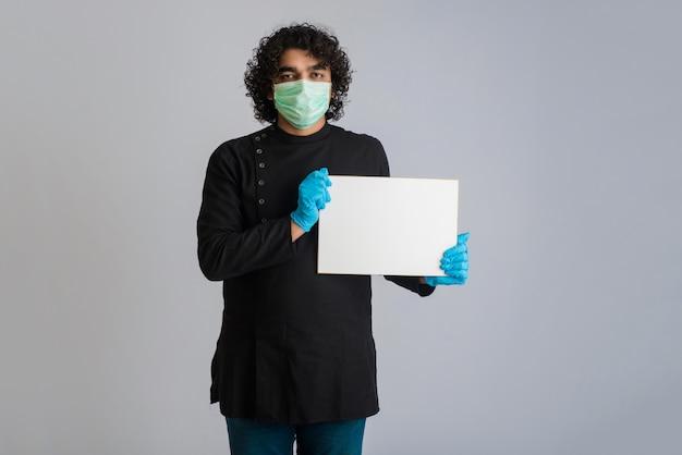 Молодой человек в медицинской маске держит и показывает пустую доску