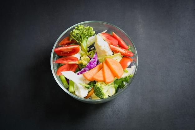 健康食品はテーブルにあり、ガラスの弓で新鮮な野菜サラダ