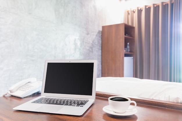 木製の机の上の白いコーヒーマグカップとラップトップ