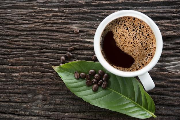パターン化された古い木の床に白いコーヒーマグカップ。