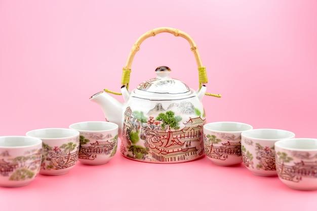 Чайник с чашками на розовом фоне.