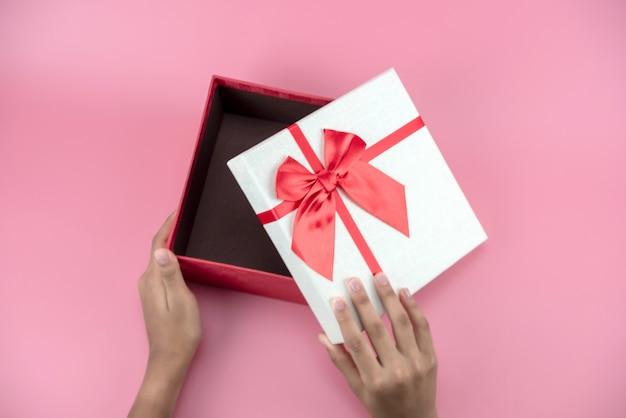 Руки держат пустую красно-белую подарочную коробку