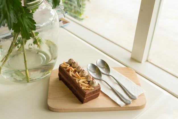 アーモンドとクリームをトッピングするチョコレートケーキ