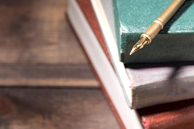 古い本のスタック上の万年筆