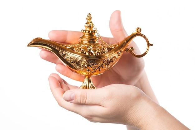 白で隔離される女性の手で魔法のランプをこすります。