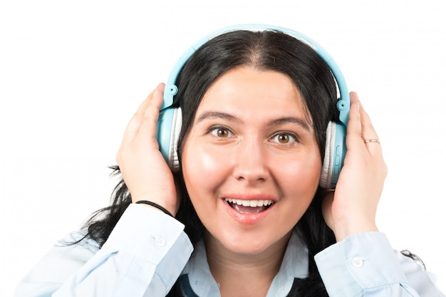 白で隔離される音楽を聴くヘッドフォンで幸せなブルネットの女性。