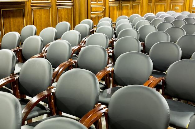 会議室に黒いモダンな椅子のアームチェア。会議室またはビジネスホールの内部