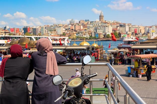 夏の晴れた日にガラタ塔とイスタンブールのパノラマを見ているイスラム教徒の女性。イスタンブール、トルコ。