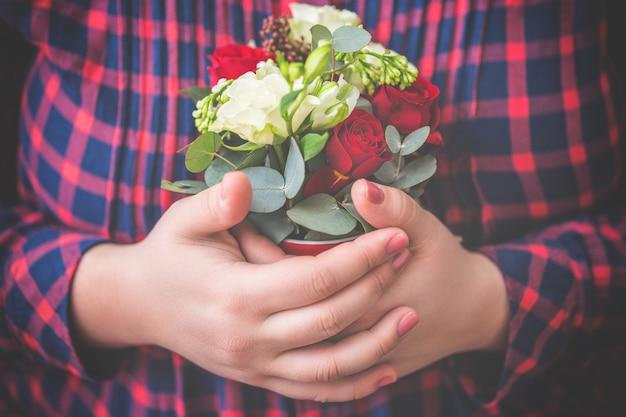 女性の手で花のクローズアップ。