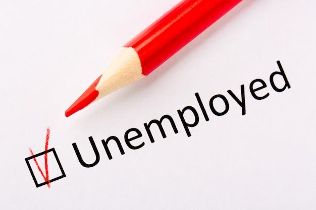赤鉛筆と白い紙の上のチェックマークと失業者の碑文。