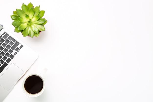 ポットと白い背景の上のコーヒーカップの植物とラップトップコンピューター。