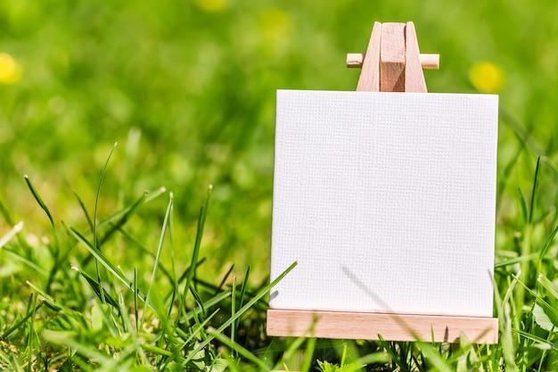 Пустая табличка на зеленой траве природы луг.