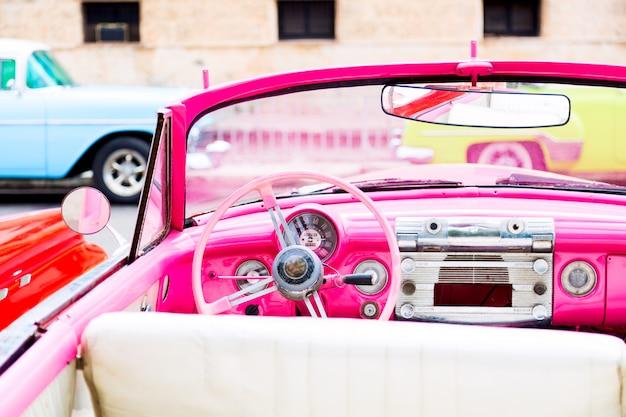 Розовый винтажный классический интерьер американского автомобиля, припаркованного на улице старой гаваны
