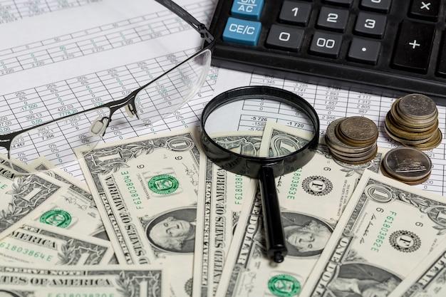 Крупным планом очки, увеличительное стекло и монеты на бумаге с цифрами