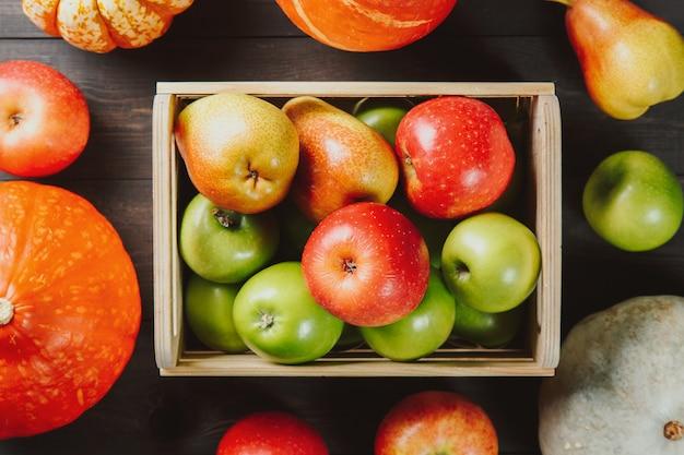 Спелые яблоки в коробке с тыквами и грушами на темном деревянном
