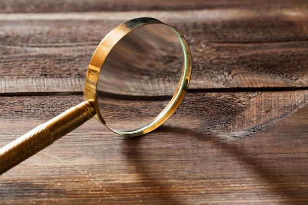 木製の背景に影と金の虫眼鏡