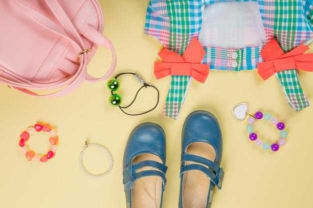 カラフルなドレス、サークレット、ネクタイ、靴が付いたピンクのバッグ