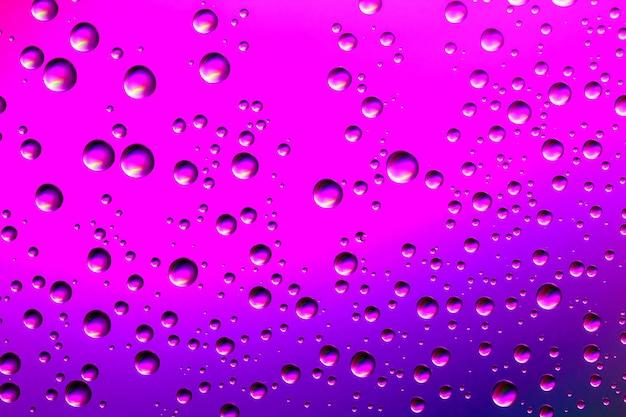 異なるサイズの水滴からの素敵なピンクと紫のグラデーションカラーの背景。抽象的な水滴の背景。