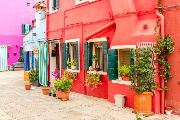 イタリア、ベニス近くのブラーノ島の植物と美しいカラフルな赤い小さな家
