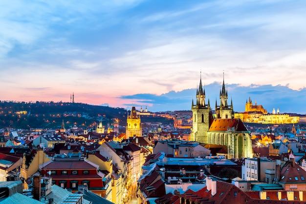 プラハ城と日没時にチェコ共和国の聖母ティンの教会の素晴らしい街並みの眺め