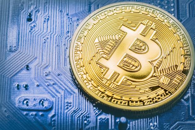 青いコンピューター回路のマザーボード上のビットコインをクローズアップ