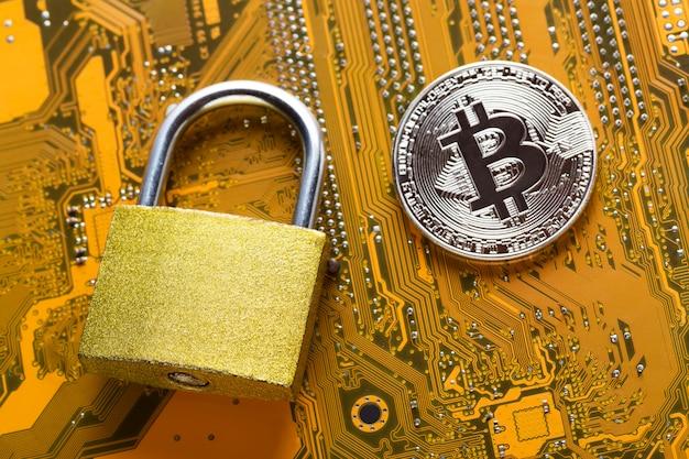 コンピューターのマザーボード上の南京錠付きビットコイン。暗号通貨インターネットデータプライバシー情報セキュリティの概念。