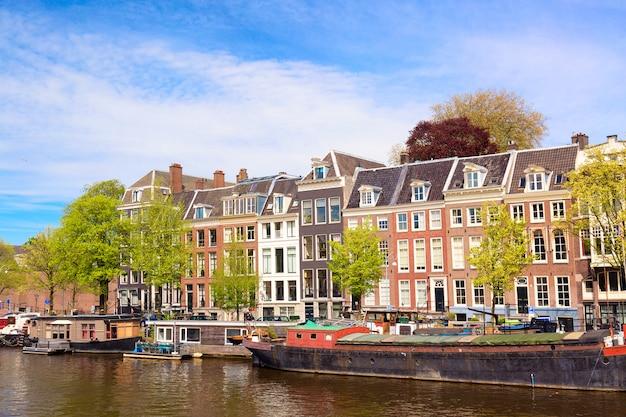 青い空、家のボート、伝統的な古い家と夏のアムステルダムの運河の都市景観ビュー
