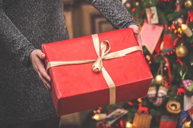 驚くべきクリスマスツリーに対して大きな赤いギフトボックスを保持している女性。