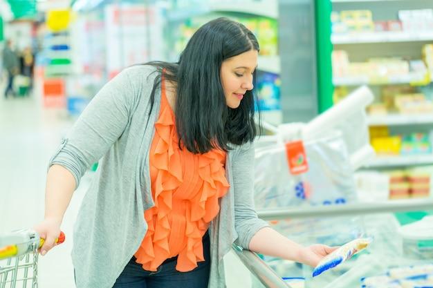 スーパーマーケットの店で商品を選んで服用する女性。