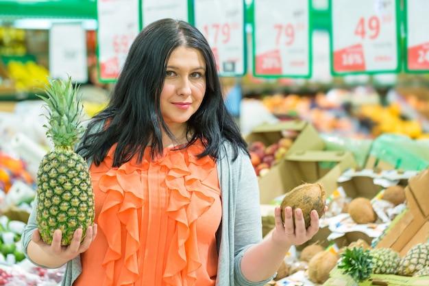 スーパーマーケットの店でパイナップルとココナッツを持つ女性の笑みを浮かべてください。