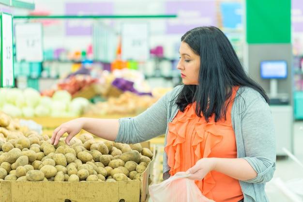 スーパーマーケットの店でジャガイモを選ぶ女性。