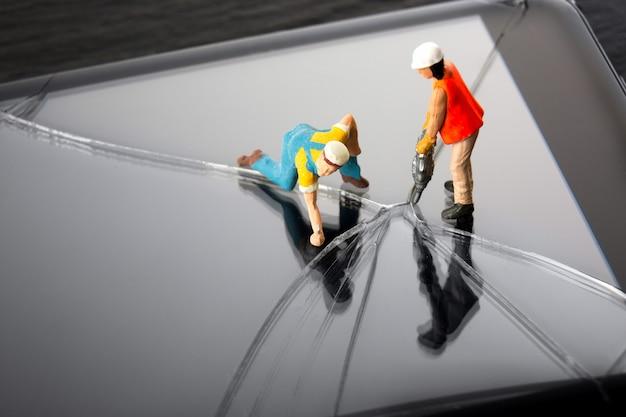ひびの入ったスマートフォンの画面を修理するミニチュア技術者。