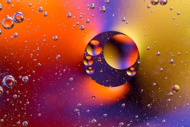 カラフルなグラデーション色と抽象的な背景。水は抽象的なサイケデリックなイメージで油を落とします。