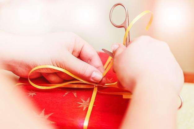 Творческое хобби поделок. изготовление ленты ручной работы с помощью ножниц. женские руки с ножницами и красной подарочной коробке крупным планом.