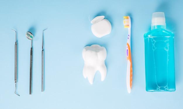 Профессиональные стальные стоматологические инструменты с зеркалом возле модели белого зуба, зубная щетка, зубная нить и жидкость для полоскания рта на голубом столе.