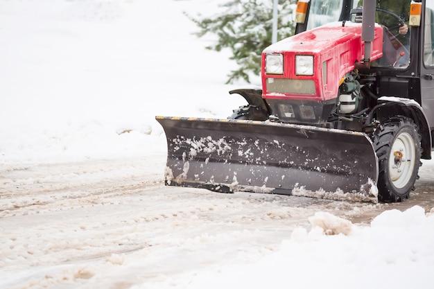 降雪後の都市で大量の雪の通りを掃除する赤いトラクター。冬時間の概念。